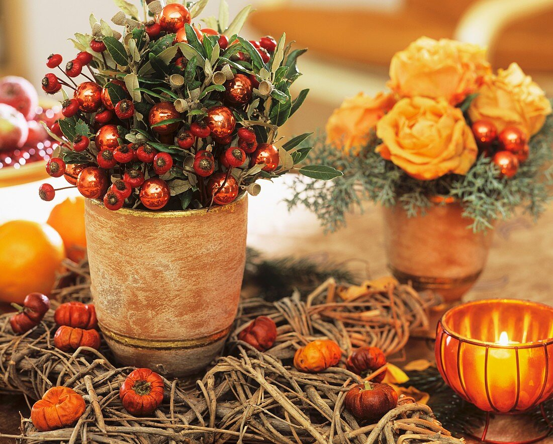 Pot of rose hips, bay leaves, glass baubles and roses