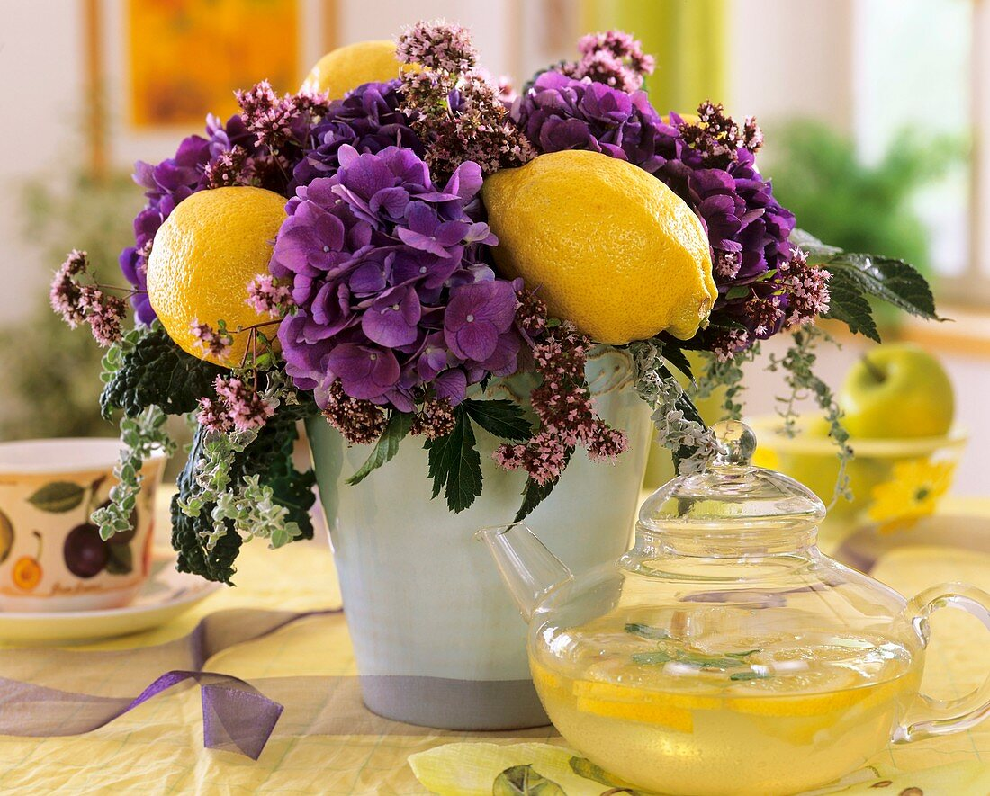 Arrangement of hydrangeas, cabbage leaves, oregano & lemons