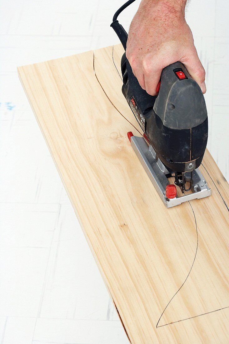 Making a wall table (shaped table legs being cut out of wood with a jigsaw)