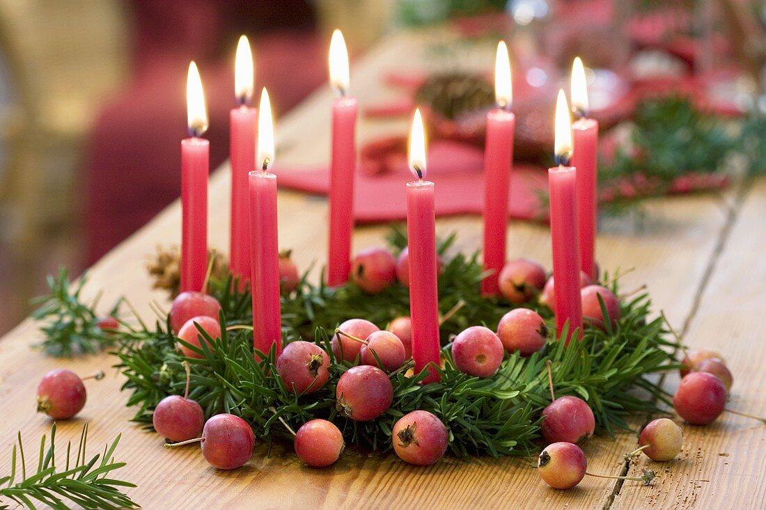 Weihnachtskranz aus Eibe mit Zieräpfeln und acht roten Kerzen