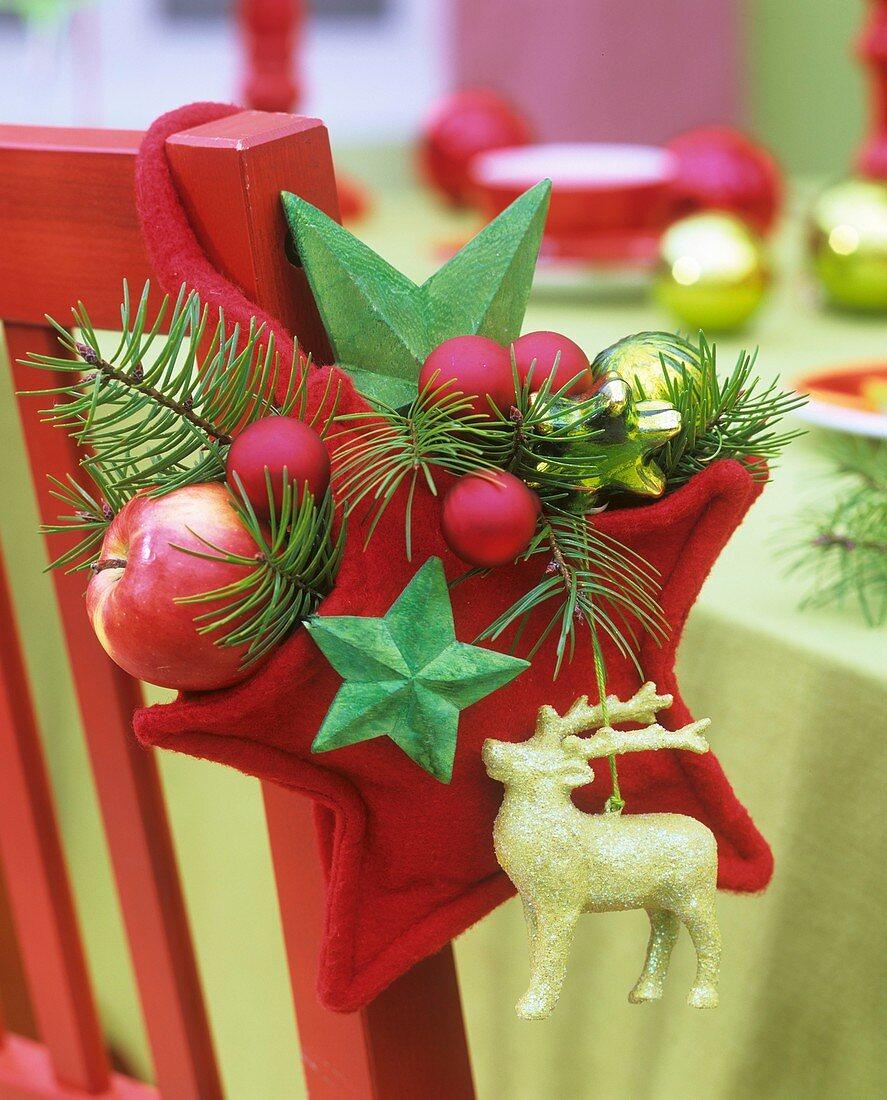 Red felt star with Douglas fir, apple, bauble on chair back