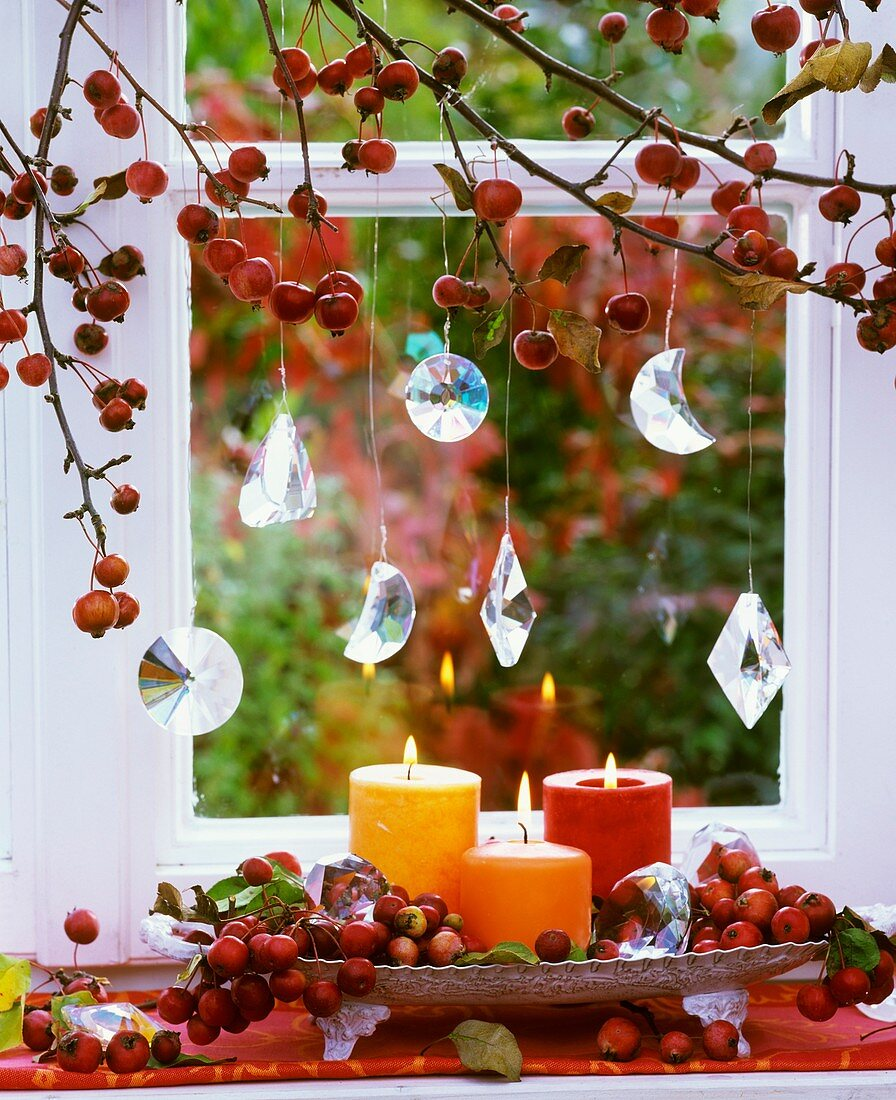 Crab apples, crystal drops and candles at window