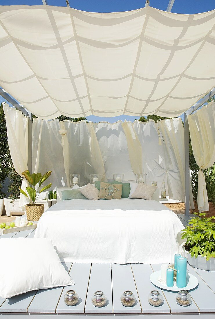 Shady wooden terrace in garden with awning above French bed