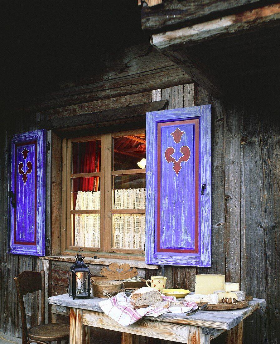 Verschiedene französische Bergkäse vor einem Holzhaus