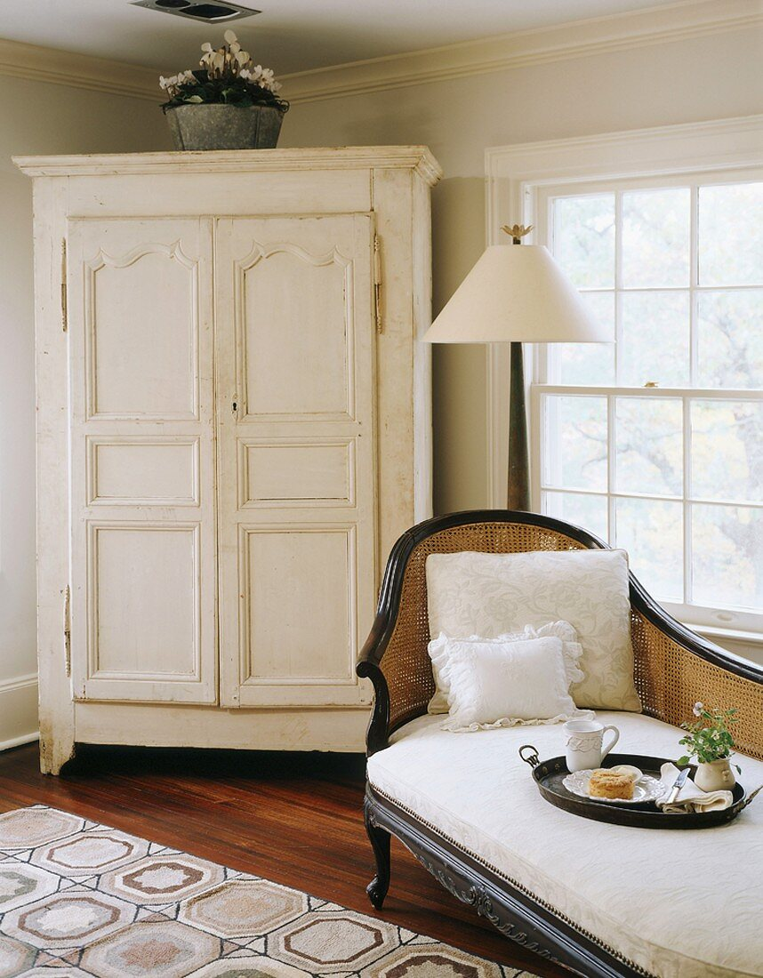 White, country-house-style cupboard and antique recamier with cane backrest in corner