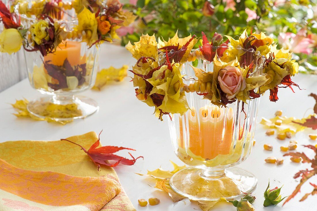 Candles in glasses with wreaths of roses, autumn leaves & corn kernels