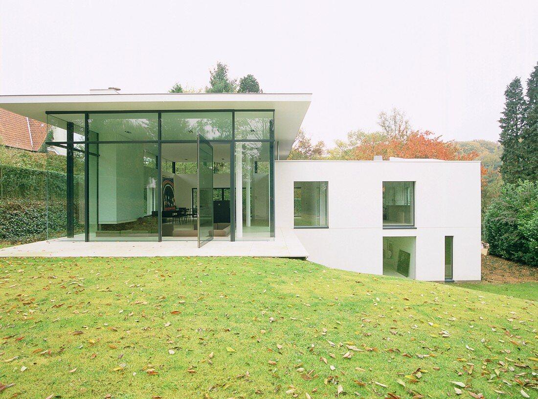 Zeitgenössisches Wohnhaus im Stil der Moderne mit aufgeglaster Fassade und versetzten Ebenen am Hang