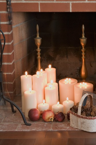 Candles, pomegranates and cones in front of fireplace