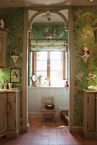 Green wallpaper with pattern of flowers & birds in bathroom