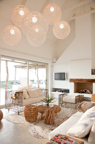 Sunny room with fireplace, airy, spherical lamps and delicate, metal sofa set with thick seat cushions