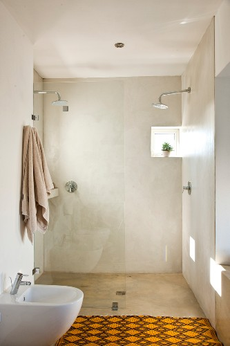 Simple shower room with two shower heads, glass partition and tiny window; yellow and brown carpet in foreground