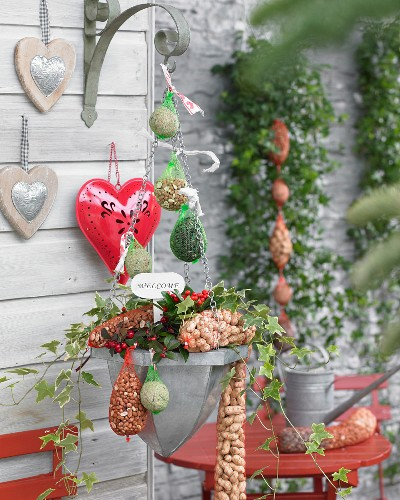 Bird food in red plastic nets, decorative hearts and flower arrangement