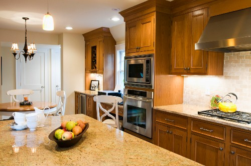 Spacious country-house kitchen with solid wood cupboard doors and large stone worksurface in foreground