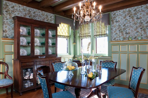 Antique dining table and chairs with elegant upholstery in front of display cabinet against painted wood panelling in traditional dining room
