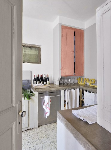 View though open door of kitchen counter and fitted cupboard with pink doors in simple interior