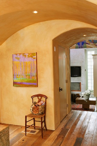 Foyer with yellow-painted vault and view into living room through ceiling-high open doorway