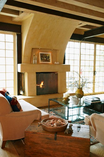 Old wooden trunk between couch and armchair around glass table and open fireplace in living room with lattice terrace doors