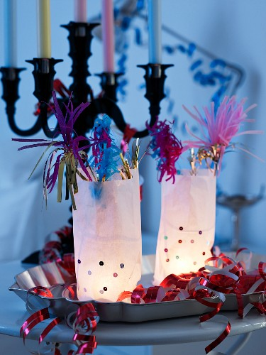 Paper-bag lanterns with party decorations on metal dish in front of multi-armed candlestick