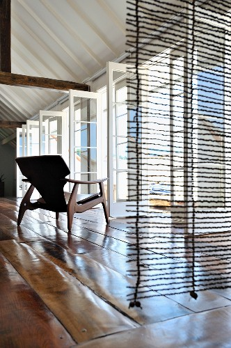 View through a transparent room divider of a 50's style wood frame chair with open patio doors and rustic wood flooring