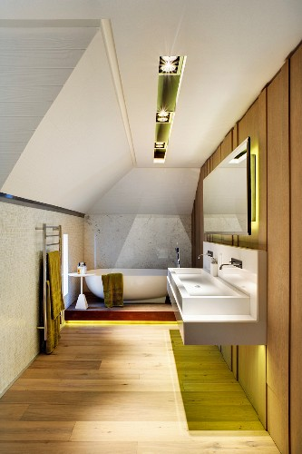 Wood on the walls and floor in a long designer bathroom with sophisticated recessed lighting