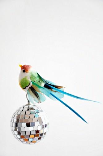 Colourful bird ornament on mosaic mirror disco ball