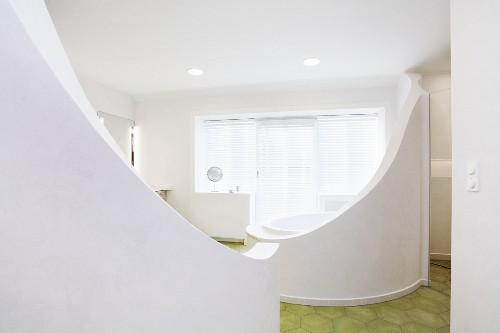 Original bathroom design - round bathtub with curved, white screen