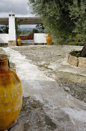 Rustic courtyard with yellow amphorae; pergola with bench in background
