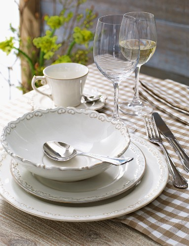 Tableware with a soup bowl and wine glasses on a checked tablecloth