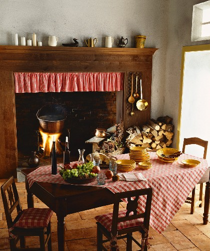 Rustic hearth in open fireplace with wooden surround in traditional kitchen; polenta cooking in pot over open fire