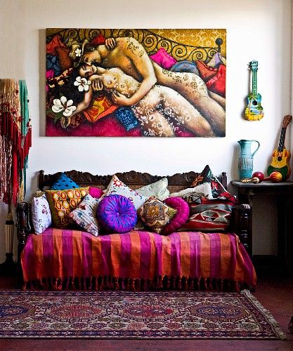 Antique sofa with colourful collection of blankets and cushions below painting of couple embracing