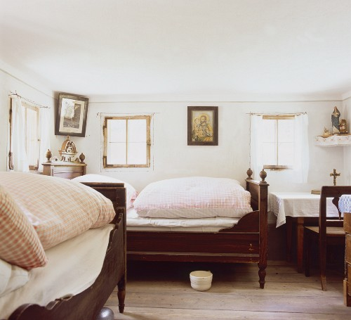 Farmhouse bedroom with chamber pot under feather bed and icons on walls