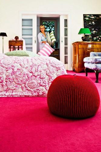 Merino wool pouffe on deep pink carpet in bedroom