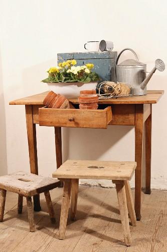 Offene Schublade mit Tontöpfen und Frühlingsblumen neben Giesskanne auf schlichtem Holztisch; davor Schemel auf Dielenboden