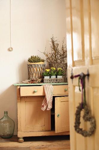 Blick durch offene Tür auf rustikale Kommode mit Blumentöpfen und Zweigen in Körben