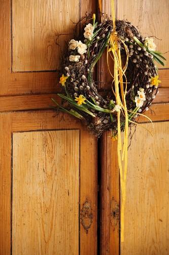 Frühlingskranz aus Birkenzweigen, Palmkätzchen und Frühlingsblumen an Schranktür gehängt