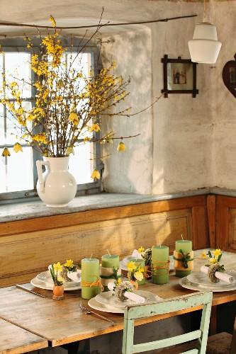 Essplatz mit Gedecken und Blumendeko vor Fenster; in Porzellankrug Forsythien auf Fensterbank