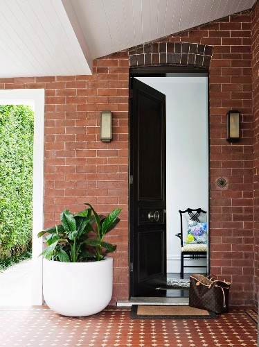 Roofed entrance area with brick facade and doorway leading to garden; open front door showing view into house