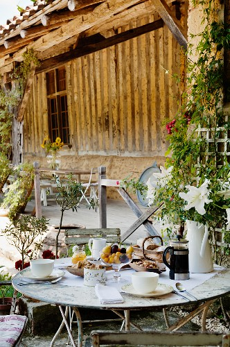 Outdoor table set for afternoon coffee in front of old barn