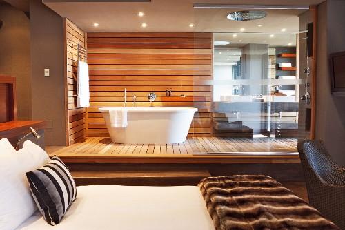 Bedroom with designer, open-plan ensuite bathroom; free-standing, white bathtub against wood-clad wall