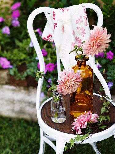 Flowers in vintage glass bottles on white chair