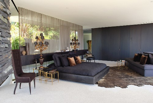 Black double bed and animal-skin rug on floor of spacious bedroom; armchair with tall backrest against stone wall to one side
