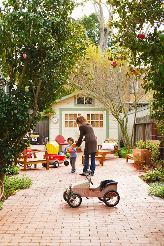 Mother and child surrounded by seating and toys in courtyard