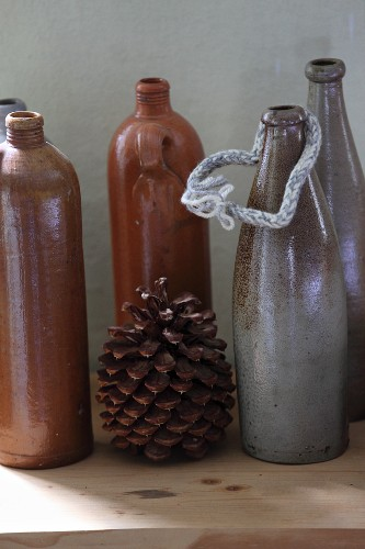 Vintage ceramic bottles in shades of brown and grey and pine cone