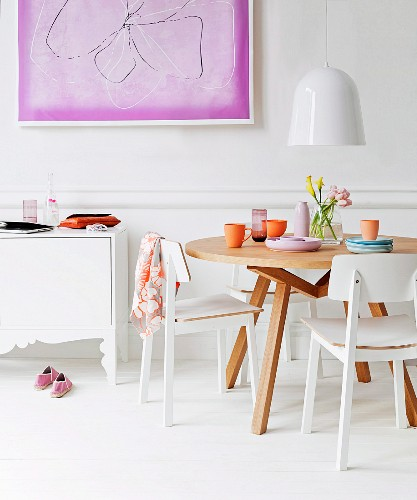 Purple picture on white wall in feminine interior with white sideboard and round dining table