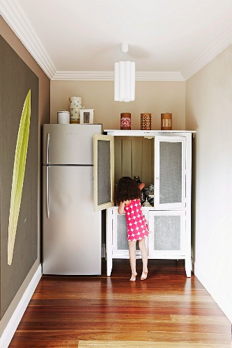 Little girl at cupboard next to fridge combination