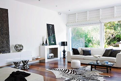 Elegant living room with light sofa, zebra skin and patio door