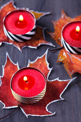 Painted autumn leaves used as coasters for tealights covered in washi tape
