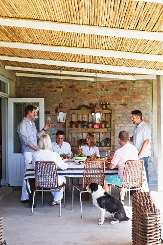 Group of friends sharing relaxed meal on roofed terrace with bamboo covering
