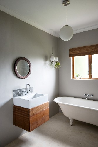 Modern sink with wooden base unit and minimalist, mosaic-tiled splashback below round mirror on wall painted pale grey; free-standing bathtub below window