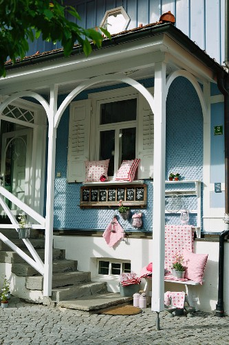 Romantic entrance to renovated country house with pale blue clapboard facade and red and white cushions on white bench